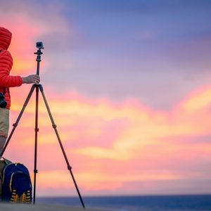 Photographer in red jacket with hood filming with small action camera on the tripod beautiful sunrise on the sand dunes in the early morning. Time lapse filming process